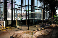 Plant History Glasshouse (formerly Australian Glasshouse), 1830s, Rohault de Fleury, Jardin des Plantes, Museum National d'Histoire Naturelle, Paris, France. Detail of the new double door system to the glasshouse. Through the glass and metal structure the New Caledonia Glasshouse (formerly Mexican Hothouse), 1834, Charles Rohault de Fleury, is visible in the background, lit by the afternoon sun.