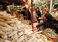Parisians shopping for food at outdoor shop with large pile of sausages in foreground, Paris, France. Paris, France.