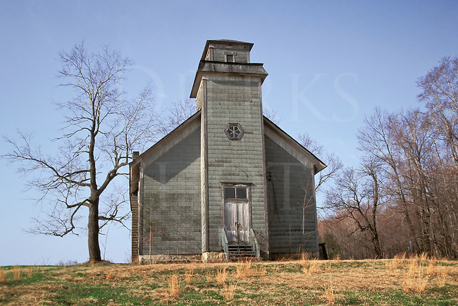 Picture of an abandoned rural church at the edge of fallow farm field in spring.