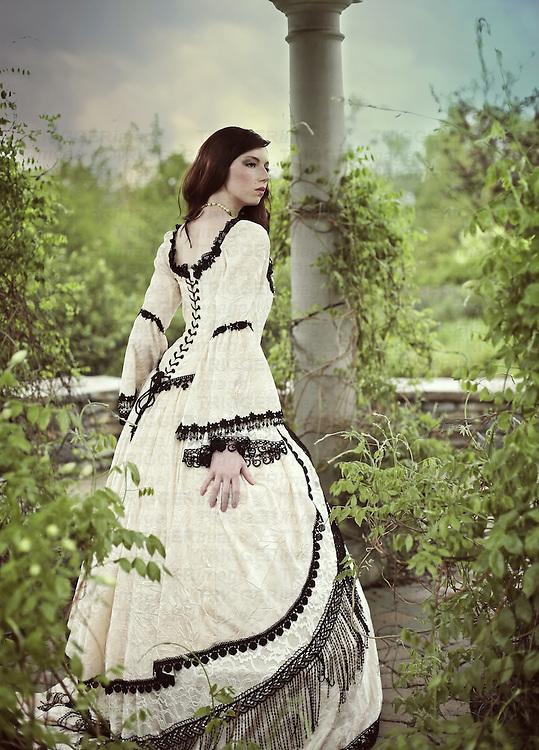 A young woman wearing a fancy renaissance dress in a garden gazebo looking startled