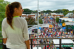Sept. 22, 2012 - Bellmore, New York U.S. - View from above of the 26th Annual Bellmore Family Street Festival, from elevated train platform of Bellmore Long Island Railroad station (LIRR), with young woman standing on platform and looking east, the direction train comes from on that track. More people than the well over 120,000 who attended last year are expected, according to the Festival Coordinator.