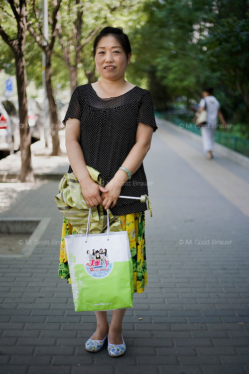 Longlanting, a beautician, age 54, poses for a portrait in Beijing. Response to 'What does China mean to you?': 'The People's Republic of China represents world peace.'  Response to 'What is China's role in the future?': 'I hope China will be a powerful country with a developed economy and culture.'