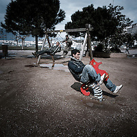 Young Afghan refugees spend time at a kids park next to the port. Patras is home to about 3,000 illegal immigrants. Most of them are Afghans, although there are also some Iranians and Uzbeks. They stop in Patras to try and find passage to various European destinations by hiding in ships, containers and trucks parked in the port. If they are lucky they will make it to their destination. Many of them live in shacks made from cartons, plastic and wood they found on the beach. To shelter from the cold they also squat in abandoned buildings, living without water and electricity. The living conditions are inhumane and unhygienic.