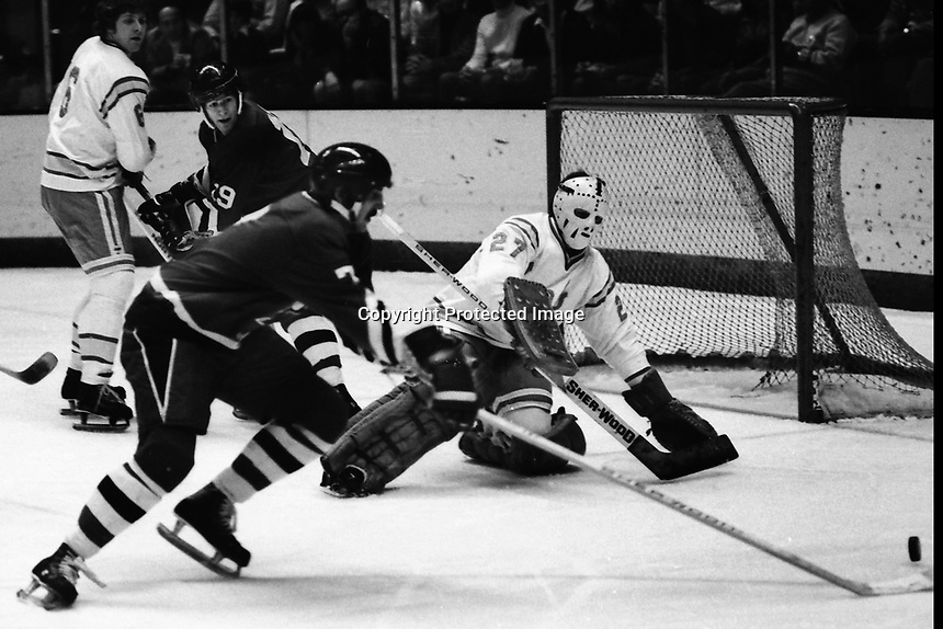 Seals vs Pittsburg Penguins 1975. Steve Durbano shoots on Seal goalie Gilles Meloche. Len Frig, in background (photo/Ron Riesterer)