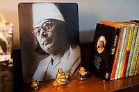 An iconic photo of Nazrul Islam, Anindita Kazi's grandfather, displayed on her reading desk that is decorated with laughing buddhas next to Rabindranath Tagore and Nazrul Islam's images and books, in her house in Calcutta, West Bengal, India, on 17th January, 2012. The West Bengal government's attempts to rename one of its historic buildings after a Bengali poet has met with controversy. Kazi Nazrul Islam, Bangladesh's national poet's legacy has always been debated, including his relationship with other Indian intellectuals such as Rabindranath Tagore, who won the Nobel Prize for Literature in 1913. In an attempt to quell doubts, Anindita Kazi, Mr Islam's grand daughter will release a CD in which she reads from unpublished letters between the two poets to show their regard for each other. Photo by Suzanne Lee for The National (online byline: Photo by Szu for The National)