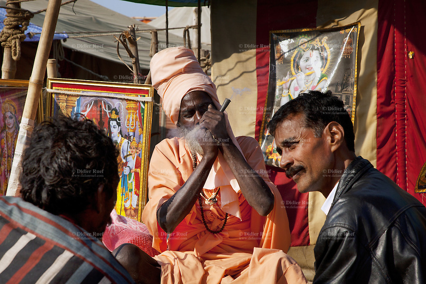 """India. Uttar Pradesh state. Allahabad. Maha Kumbh Mela. A Sadhu sits and smokes a shilom with hashish outside his tent in Sangam. Both men are visitors and wait to smoke the drug. Two drawings, one of Shiva (left) and Krishna (right). Shiva is a Hindu deity. Krishna is another Hindu deity, one of the """"avatars"""" (or """"incarnation"""") of Vedic Supreme God Vishnu or Narayana. The Kumbh Mela, believed to be the largest religious gathering is held every 12 years on the banks of the 'Sangam'- the confluence of the holy rivers Ganga, Yamuna and the mythical Saraswati. In Hinduism, Sadhu (good; good man, holy man) denotes an ascetic, wandering monk. Sadhus are sanyasi, or renunciates, who have left behind all material attachments. They are renouncers who have chosen to live a life apart from or on the edges of society in order to focus on their own spiritual practice. A Sadhu is usually referred to as Baba by common people. The Maha (great) Kumbh Mela, which comes after 12 Purna Kumbh Mela, or 144 years, is always held at Allahabad. Uttar Pradesh (abbreviated U.P.) is a state located in northern India. 10.02.13 © 2013 Didier Ruef"""