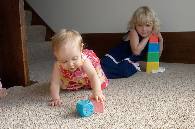 Berkeley CA Sisters nine-months old and four, baby crawling toward toy while sister protects her construction  MR