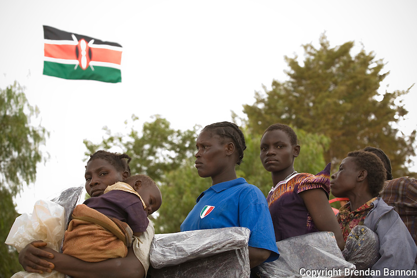 Kenyan's dispalaced by post-election violence wait for food rations under the national flag at a camp in Endebess, Kenya. 2008...
