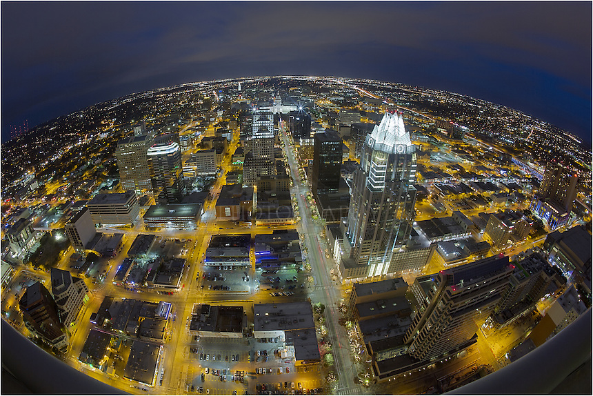 Taken from 54 stories high, this image looks over Austin, Texas. You can see Congress Avenue, lined with festive lights, leading to the Christmas tree at the Texas Capitol. In the distance is the University of Texas Tower. Closer is the distictive Frost Tower.