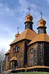 Ancient wooden church house under blue clear sky Ukraine Eastern Europe Spring countryside scenic Vertical orientation