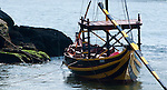 Old port boat used to transport wine barrels sitting on the Douro River in Porto, Portugal.