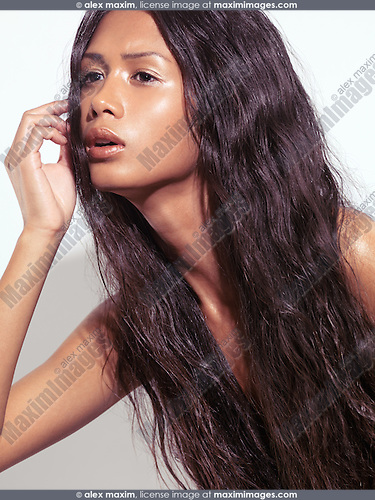 Sensual beauty portrait of a glamorous young woman with long brown hair and shiny skin