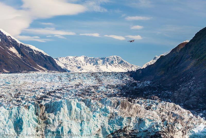 Bush plane flies over Cascade glacier,  Barry Arm, Prince William Sound, southcentral, Alaska.