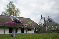 Girl wearing traditional dress dances after being watered by buckets of water splashed on her as part of the fertility traditions during the Easter watering celebration in the Skansen open air ethnographic museum in Szenna (about 200 km South-West of capital city Budapest), Hungary on April 14, 2017. ATTILA VOLGYI