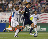 New England Revolution forward Milton Caraglio (9) dribbles as San Jose Earthquakes defender Jason Hernandez (21) defends. In a Major League Soccer (MLS) match, the San Jose Earthquakes defeated the New England Revolution, 2-1, at Gillette Stadium on October 8, 2011.