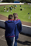 Harestanes AFC v Girvan FC, 15/08/2015. Scottish Cup preliminary round, Duncansfield Park. Two boys watching home players taking part in their pre-match warm-up on the pitch before Harestanes AFC take on Girvan FC in a Scottish Cup preliminary round tie, staged at Duncansfield Park, home of Kilsyth Rangers. The home team were the first winners of the Scottish Amateur Cup to be admitted directly into the Scottish Cup in the modern era, whilst the visitors participated as a result of being members of both the Scottish Football Association and the Scottish Junior Football Association. Girvan won the match by 3-0, watched by a crowd of 300, which was moved from Harestanes ground as it did not comply with Scottish Cup standards. Photo by Colin McPherson.