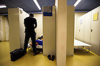 Switzerland. Geneva. A homeless black man from Africa is preparing his bed in the fallout shelter Richemont. The bunker was constructed as civil defense measures during the Cold War and is a unit of the Civil Protection. Switzerland is unique in having enough nuclear fallout shelters to accommodate its entire population. 7.02.2014 © 2014 Didier Ruef
