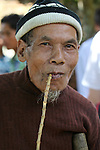 A villager maimed by a land mine explosion poses for a portrait in A Luoi, Vietnam. The ethnic minority man smokes a traditional long-stemmed pipe. People in the A Shau valley are often maimed or killed when they try to salvage mines and other bombs left over from the war for scrap metal. April 25, 2013.
