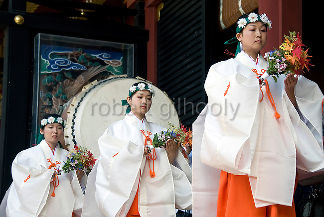 Maiko shrine attendants prepare to perform a dance during a ritual inside the inner sanctuary during the annual Reitaisai Grand Festival at Tsurugaoka Hachimangu Shrine in Kamakura, Japan on  14 Sept. 2012.  Sept 14 marks the first day of the 3-day Reitaisai festival, which starts early in the morning when shrine priests and officials perform a purification ritual in the ocean during a rite known as hamaorisai and limaxes with a display of yabusame horseback archery. Photographer: Robert Gilhooly