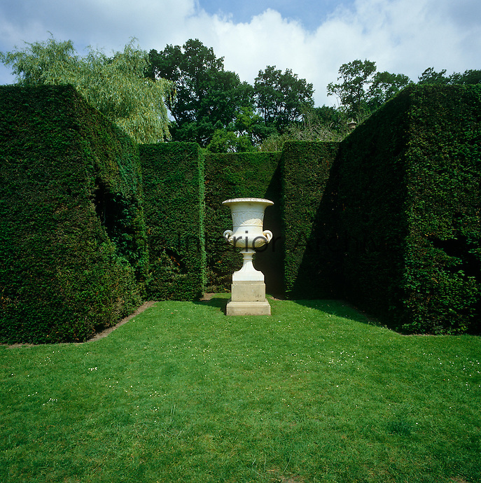 A large marble urn surrounded by tall yew hedges