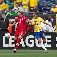 Canadian midfielder Sophie Schmidt (13) passes the ball as Brazilian player Gabriella Demoiser (21) defends. In an international friendly, Canada defeated Brasil, 2-1, at Gillette Stadium on March 24, 2012.