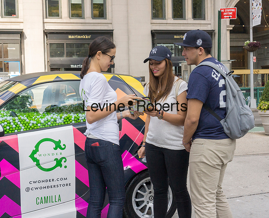 Workers for the store C. Wonder engage with consumers and collect data using an iPad at an event in Madison Square in New York on Saturday, September 20, 2014. C. Wonder was promoting their new store in the Flatiron neighborhood using decorated Smart Cars, one filled with gumballs for visitors to guess the amount.  (© Richard B. Levine)