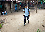 Eleven-year old Juan Lopez walks with a white cane at his home in Zipolite, a town in Oaxaca, Mexico. Juan is blind, and yet refuses to be sidelined. He rides his bike, for example, with his sister's help. She perches on the back and signals him which way to steer by pinching his shoulder. If she pinches his right shoulder, for example, he goes right. The harder the pinch, the sharper the turn.