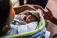A survivor of the Zamboanga City rebel attack brings her 7-month-old premature-born baby to the medical tent in the city's largest stadium in Zamboanga, Mindanao, The Philippines on November 4, 2013. These Internally Displaced People (IDP) have set up shared tents along the running track and in the breachers in this stadium after surviving the 3 week long attack by MNLF rebels. Photo by Suzanne Lee for SPRINT-IPPF