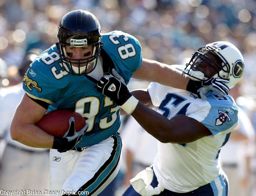 Jacksonville Jaguar tight end Pete Mitchell (#83) fights off a Tennessee Titan defender after catching a pass during a game in Jacksonville, FL on Sunday, December 22, 2002.  Tennessee won the game 28 to 10. (Photo by Brian Cleary/www.bcpix.com)