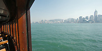 Looking back across the water to the Hong Kong island skyline from inside a Star Ferry, mid-crossing