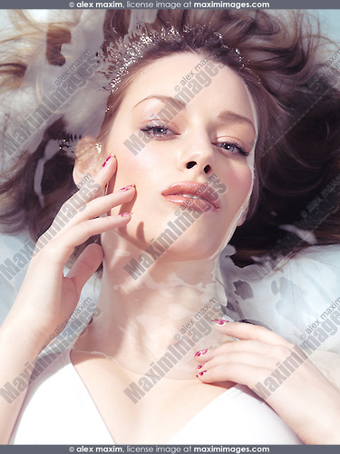 Beauty portrait of a young woman lying relaxed in water in bright sunlight. Beauty treatment concept.