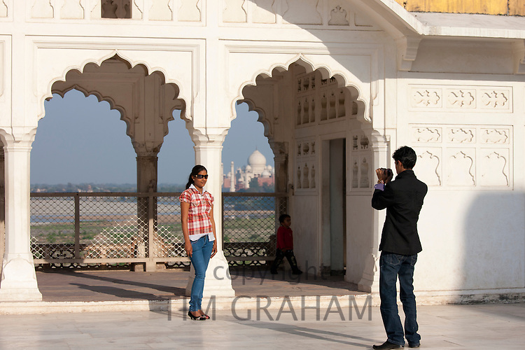 Indian girl in western clothes poses in front of view of Taj Mahal from Khas Mahal Palace at Agra Fort, India