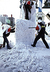 A snow sculpture team works on a block of snow. Using ice picks, chisels and hatchets, teams from around the world,  turn blocks of frozen snow into detailed scupltures. These are not traditional Frosty the Snowmen, but huge carved and chiseled Samurai Warriors, Buddhists gods, historical heroes of fairy tales and Walt Disney characters. Some stand as big as buildings. Chiseled out of tons of packed snow, the sculptures are the pride and job of the residents of Sapporo, Japan, who hosts the world famous Ice and Snow Sculpture Festival for five days in early February.Themes of the sculptures are picked from Kabuki stages, historical characters or fairy tales. (Jim Bryant Photo).....