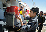 """A boy sells an iced drink on the """"Avenue des Champs-Élysées""""--the main commercial street in the Zaatari refugee camp near Mafraq, Jordan. Established in 2012 as Syrian refugees poured across the border, the camp held more than 80,000 refugees by 2015, and was rapidly evolving into a permanent settlement, with shops along this street selling everything the refugees could want. The ACT Alliance provides a variety of services to refugees living in the camp."""