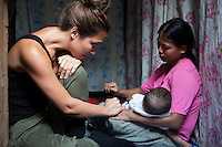 UK celebrity Myleene Klass cries as she listens to Vilma Tacuyo, 20, speak of her difficulties while she breastfeeds her youngest child, Ulderico (10 months), in their one room home in an urban slum in Paranaque City, Metro Manila, The Philippines on 18 January 2013. Vilma had raised her first 3 children on formula and had to cut down on food for her family to afford it. Both John Ashley, 4, and Justin, 3, are malnourished and stunted, and after losing one of her children, she now breastfeeds her youngest, Ulderico. Photo by Suzanne Lee for Save the Children UK