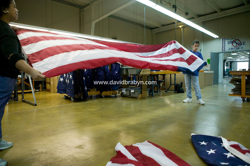 21 June 2005 - Oaks, PA - Estrellita Harris (L) and Nancy Rotay (R) fold a completed American flag at the Annin & Co. flag manufacturing plant in Oaks, PA.