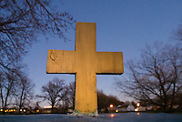 A hand-painted golden wooden cross in the yard of a church in a small neighborhood.<br />