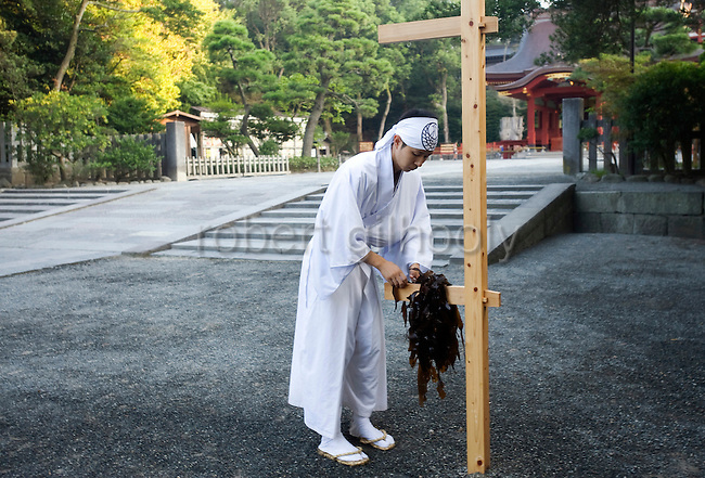A shrine priest hangs pieces of seaweed on a stand during a purification ritual known as hamaorisai at the start of the 3-day Reitaisai festival in Kamakura, Japan on  14 Sept. 2012.  As a symbol of the purification, priests collect the seaweed from the sea and take it back to the shrine, hanging pieces around the shrine grounds to appease the gods. Photographer: Robert Gilhooly