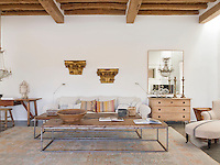 The whitewashed living room walls have been left bare save for a pair of antique gilt capitals and a mirror