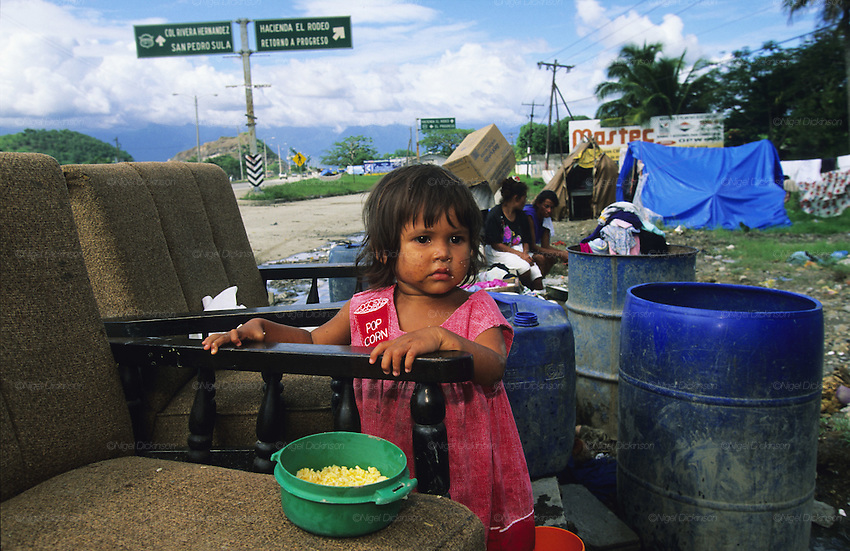 Central America, Honduras, San Pedro Sula. Devastation in the aftermath of Hurricane Mitch. High winds and flooding. Humanitarian aid efforts. Refugees. Young girl with rice, refugee camp. Infrastructure destroyed.