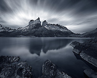 A long exposure renders cloud streaks over Los Cuernos del Paine at days end, reflected in the glacial lake below.