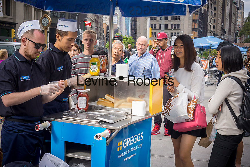 The UK bakery chain Greggs set up a hot dog cart in Madison Square in New York on Tuesday, September 16, 2014 to give away free hot dogs and to record New Yorkers' reactions. The chain is branching out from its sausage rolls and pastries and has introduced coffee and low-fat sandwiches recently. Greggs is the largest bakery chain in the UK with over 1600 outlets. The Madison Square event appeared to have been created solely for the purpose of taping New Yorker's reaction to their hot dogs, perhaps for possible use in a commercial or other advertising. (© Richard B. Levine)
