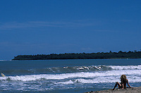 Young woman sitting on a beach in Cahuita National Park on the Caribbean coast of Costa Rica