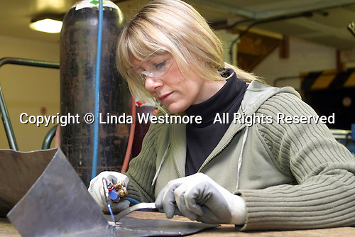 Mature student learning welding with an oxy acetylene torch, Further Education College.  She's making the lead flashings which go around the base of a chimney stack to keep the rain out.