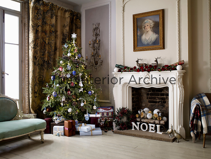 A musical wooden advent calendar and wrapped gift boxes are placed beneath a Christmas tree in this traditional London town house