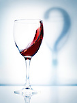 Glass of red wine and a shadow question mark artistic conceptual photo isolated on light blue background