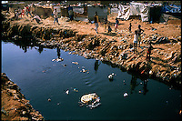 Luanda, Angola, May, 25, 2006.Porto do Pesqueiros, open air sewer; children playing in garbage and cholera infected waters. Between February and June 2006, more than 30000 people were infected with cholera in Angola's worse outbreak ever; more than 1300 died..Just 4 years after the end of a 25 year long civil war, Angola is starting to emerge again, yet a lot remains to be done: entire regions are still cut-off from the ouside world because of landmines and broken bridges, over 80% of the population lives below the poverty threshold in one of the potentially richest country in Africa. Natural ressources include oil, diamonds, gold and...water!..