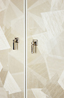 A detail of a wardrobe with a patterned finish and stainless steel handles.