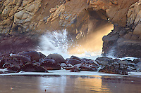 Ocean waves, mist and light stream through the portal in the Tafoni sandstone, Pfeiffer State Beach, California, USA