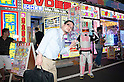 """July 23 2012, Tokyo, Japan - A Japanese costumer and a soldier of the Star Wars movie announces the """"Robot Restaurant"""" at Kabukicho in Shinjuku. The restaurant advertises that cost 10 billion yen (130 million) opening. Robots run by real women dressed in military, perform cabaret dance for its customers, opened in the Kabukicho area, Shinjuku in Tokyo. (Photo by Rodrigo Reyes Marin/AFLO)"""